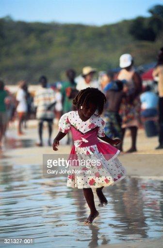 West Indies, Antigua, young girl dancing on seashore : Stock Photo
