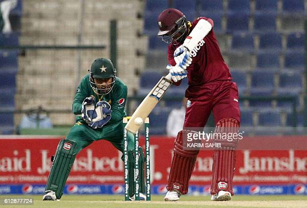 West Indies' batsman Denesh Ramdin strikes the ball as Pakistan's wicketkeeper Sarfraz Ahmed fields during the 3rd ODI cricket match between Pakistan...