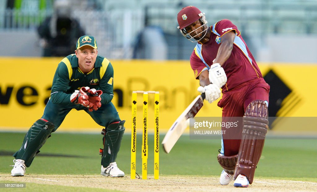 West Indies batsman Johnson Charles (R) hits over the in-field as Australian wicketkeeper Brad Haddin (L) looks on in their one-day cricket international played at the Melbourne Cricket Ground (MCG), on February 10, 2013. AFP PHOTO/William WEST IMAGE
