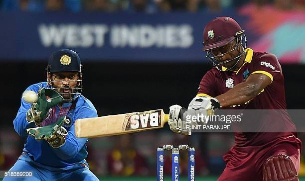 West Indies batsman Johnson Charlesplays a shot as India's captain Mahendra Singh Dhoni looks on during the World T20 cricket tournament semifinal...