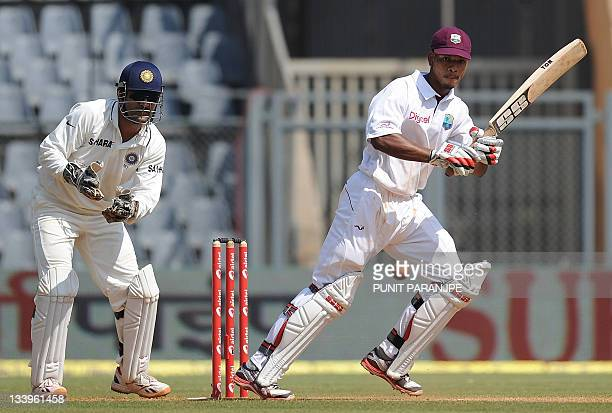 West Indies batsman Kieran Powell plays a shot as Indian captain Mahendra Singh Dhoni watches during the second day of the third test cricket match...