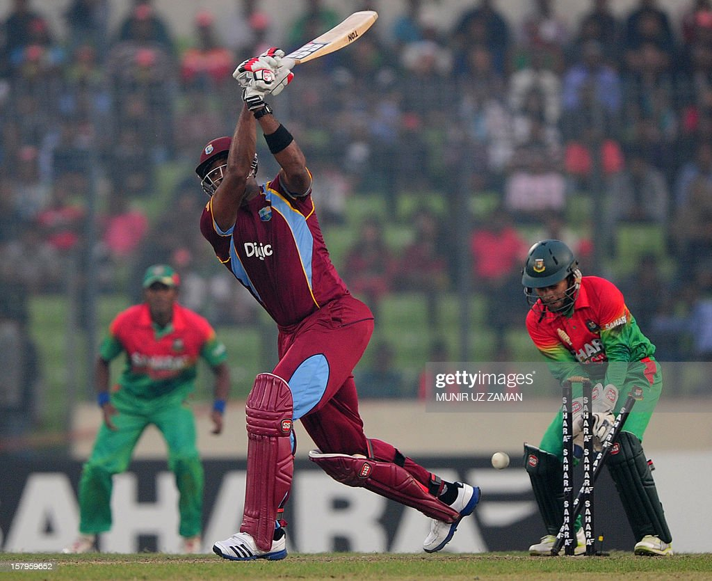 West Indies batsman Kieron Pollard (C) is bowled by the unseen Bangladesh cricketer Mominul Haque as the captain Mushfiqur Rahim (R) looks on during the fifth one day international between Bangladesh and West Indies at The Sher-e-Bangla National Cricket Stadium in Dhaka on December 8, 2012. AFP PHOTO/ Munir uz ZAMAN