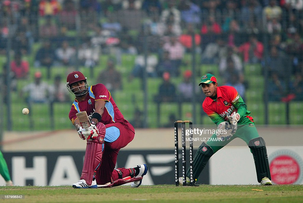 West Indies batsman Kieron Pollard (L) plays a shot as Bangladesh captain Mushfiqur Rahim looks on during the fifth one day international between Bangladesh and West Indies at The Sher-e-Bangla Nat...