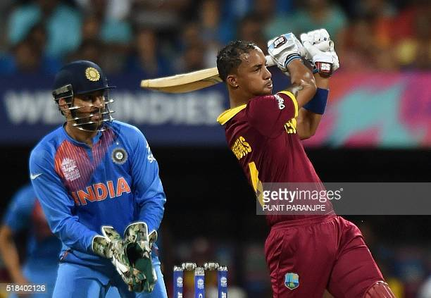 West Indies batsman Lendl Simmonsis watched by India's captain Mahendra Singh Dhoni as he plays a shot during the World T20 cricket tournament...