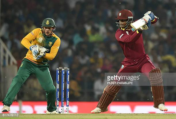 West Indies batsman Marlon Samuelsplays a shot as South Africa's wicketkeeper Quinton de Kock looks on during the World T20 cricket tournament match...