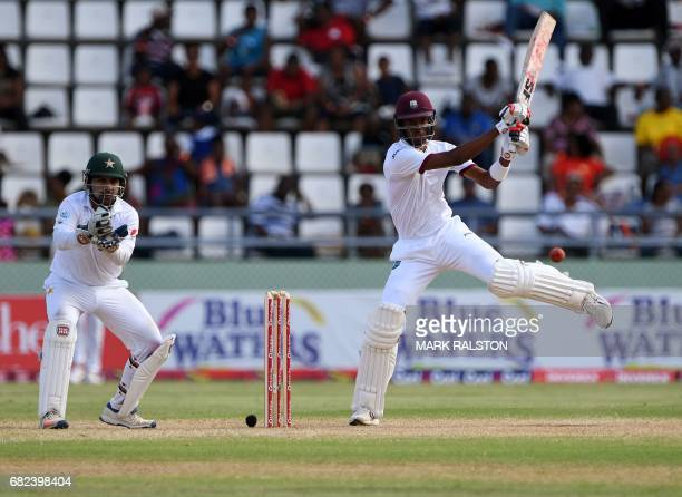 West Indies batsman Roston Chase plays a cover shot watched by wicketkeeper Sarfraz Ahmed off the bowling of Yasir Shah of Pakistan during the third...