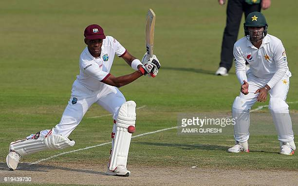West Indies' batsman Roston Chase plays a shot as Pakistani cricketer Sami Aslam looks on during the second day of the third and final Test between...