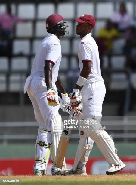 West Indies batsmen Jason Holder and Roston Chase celebrate their 50 partnership against Pakistan on the fifth day of play of the final test match at...