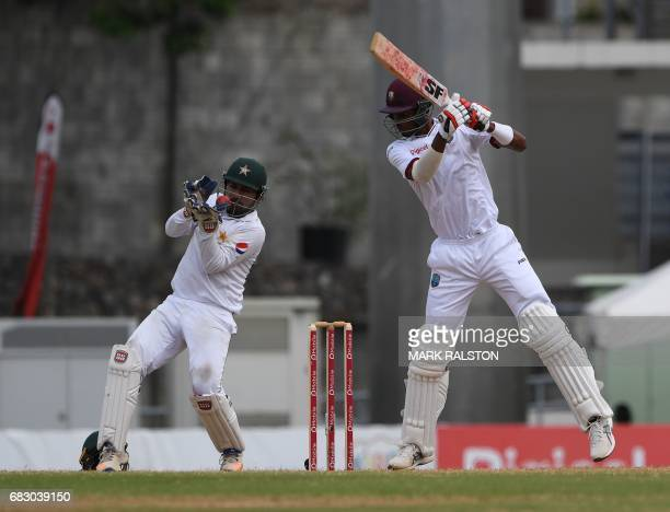 West Indies batsmen Roston Chase watches as wicketkeeper Sarfraz Ahmed of Pakistan tries to stop a ball on the fifth day of play of the final test...
