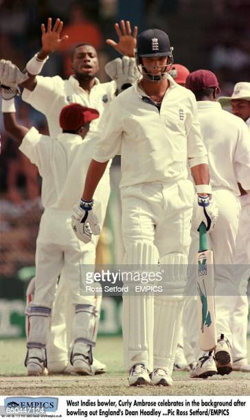 West Indies bowler Curtly Ambrose celebrates in the background after bowling out England's Dean Headley