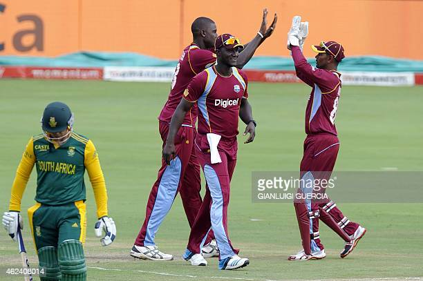 West Indies bowler Jason Holder celebrates with teammates the dismissal of South African batsman Quinton De Kock during the fifth One Day...