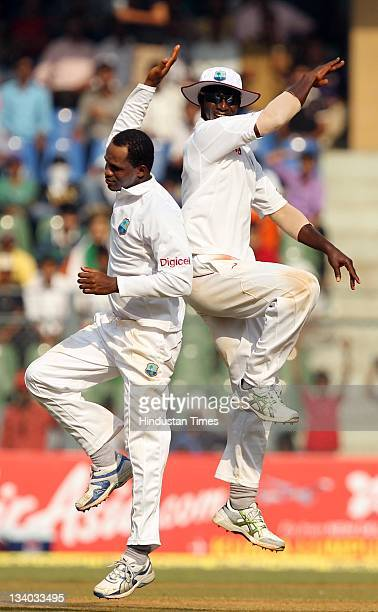 West Indies bowler Marlon Samuels celebrates with captain Drren Sammy after taking the wicket of Indian batsman Rahul Dravid during the third day of...