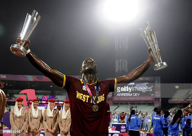 TOPSHOT West Indies captain Darren Sammy poses with a pair of trophies as he celebrates after victory in the World T20 cricket tournament final match...