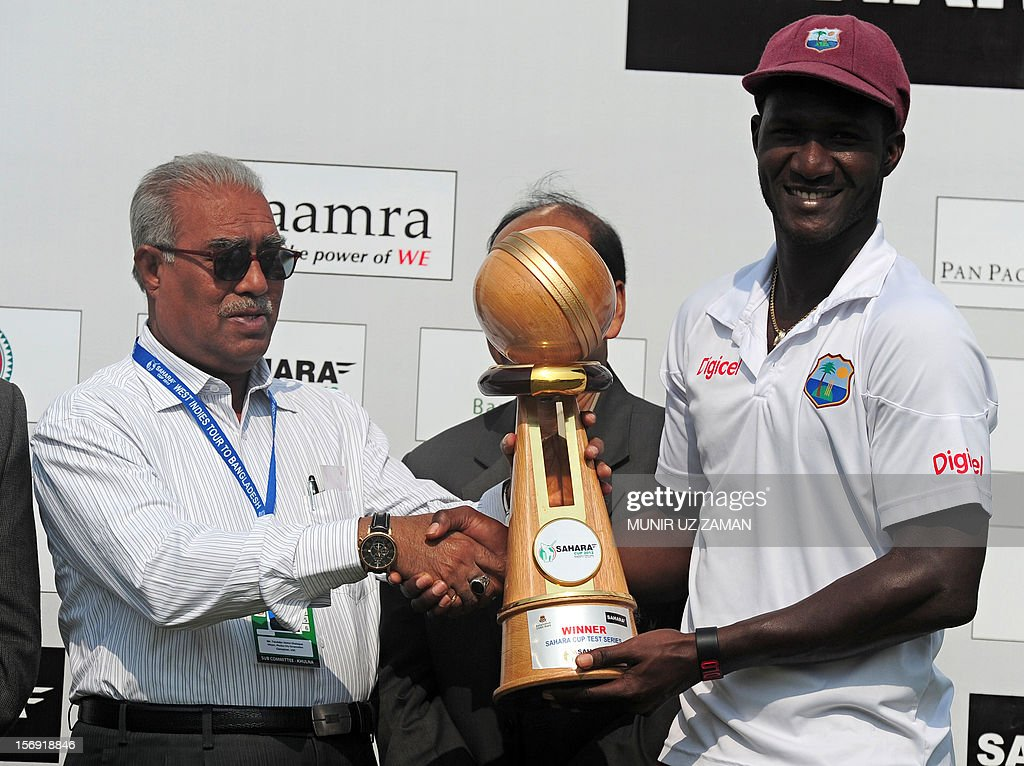 West Indies captain Darren Sammy (R) receives the tournament trophy during the fifth day of the second Test match between Bangladesh and the West Indies at the Sheikh Abu Naser Stadium in Khulna on November 25, 2012. Paceman Tino Best took a career-best six-wicket haul to fire the West Indies to a crushing ten-wicket win against Bangladesh in the second Test in Khulna on Sunday, sealing the series 2-0. AFP PHOTO/ Munir uz ZAMAN