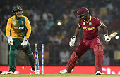 TOPSHOT West Indies captain Darren Sammylooks back at his shattered wicket as South Africa's Quinton de Kock celebrates his dismissal during the...