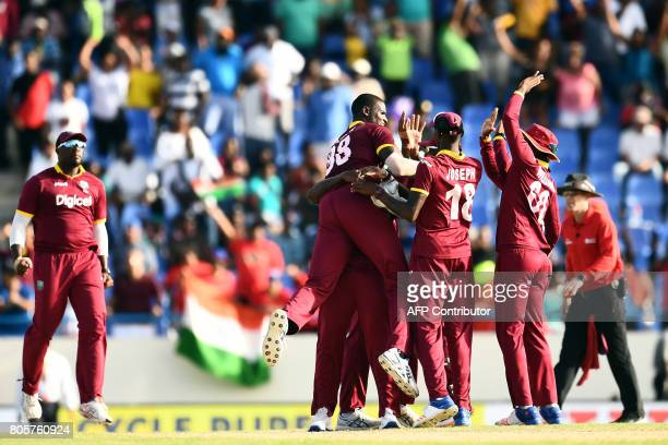 West Indies' captain Jason Holder celebrates with teammates after defeating India at the end of the fourth One Day International match between West...