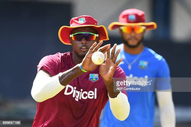 West Indies' captain Jason Holder grips a catch during a practice session at the Queen's Park Oval in Port of Spain Trinidad on June 22 ahead of the...