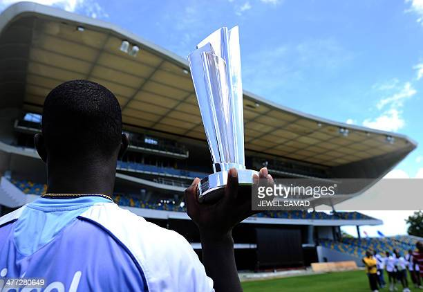 West Indies cricket team captain Darren Sammy holds up the ICC T20 World Cup trophy at the Kensington Oval in Bridgetown on March 8 2014 West Indies...