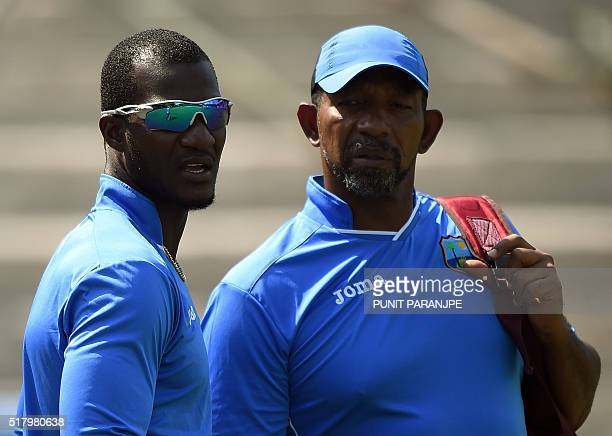 West Indies cricket team captain Darren Sammy speaks with coach Phil Simmons during the training session at the Cricket Club of India stadium in...