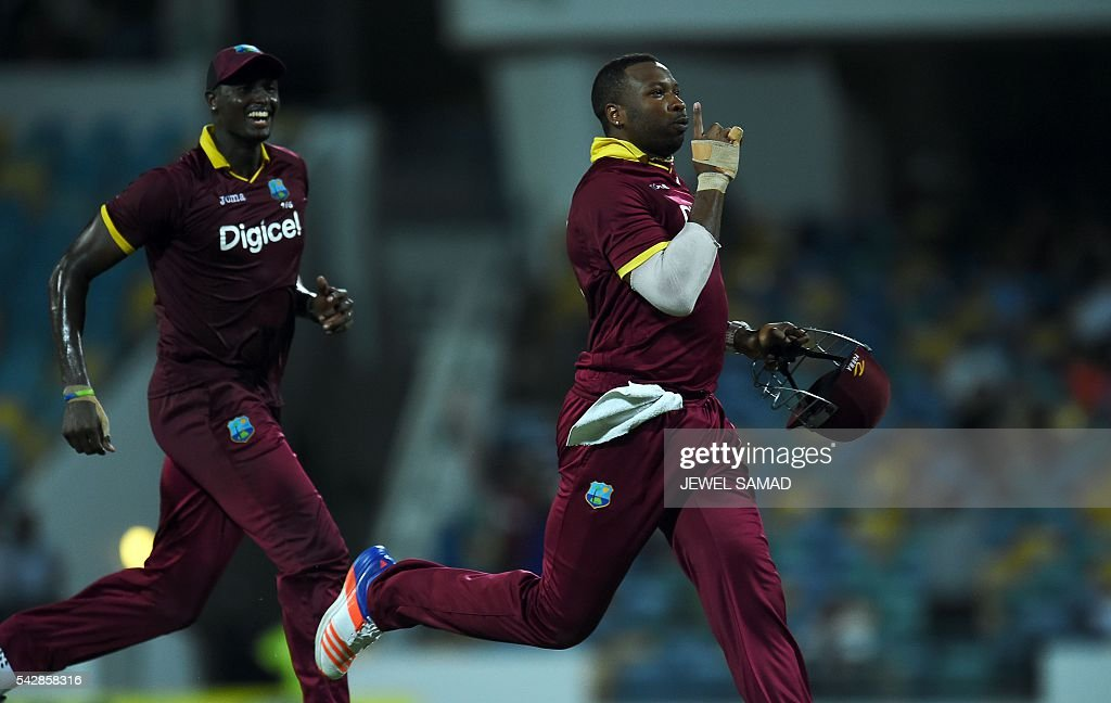 West Indies cricket team captain Jason Holder (L) and his teammate Kieron Pollard celebrate after dismissing South African batsman Chris Morris during the 9th One Day International match of the Tri-nation Series between South Africa and West Indies at the Kensington Oval stadium in Bridgetown on June 24, 2016. / AFP / Jewel SAMAD