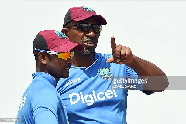 West Indies cricket team coach Phil Simmons talks to captain/wicketkeeper Denesh Ramdin during a training session at the Kensington Oval Stadium in...
