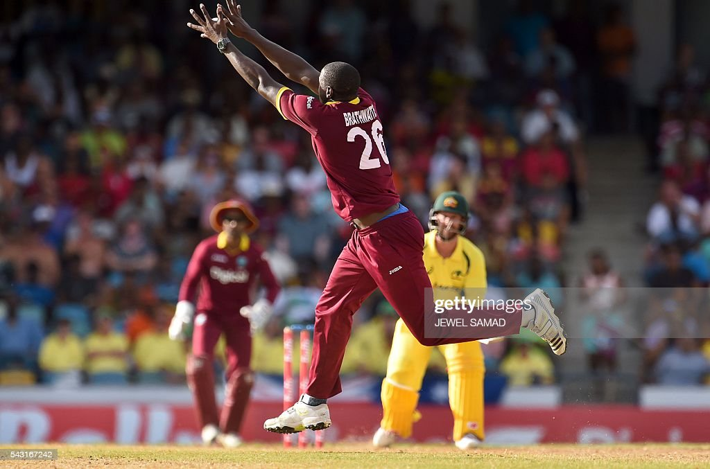 West Indies cricketer Carlos Brathwaite (C) leaps in the air to field the ball during the final match of the Tri-nation Series between Australia and West Indies in Bridgetown on June 26, 2016. / AFP / Jewel SAMAD