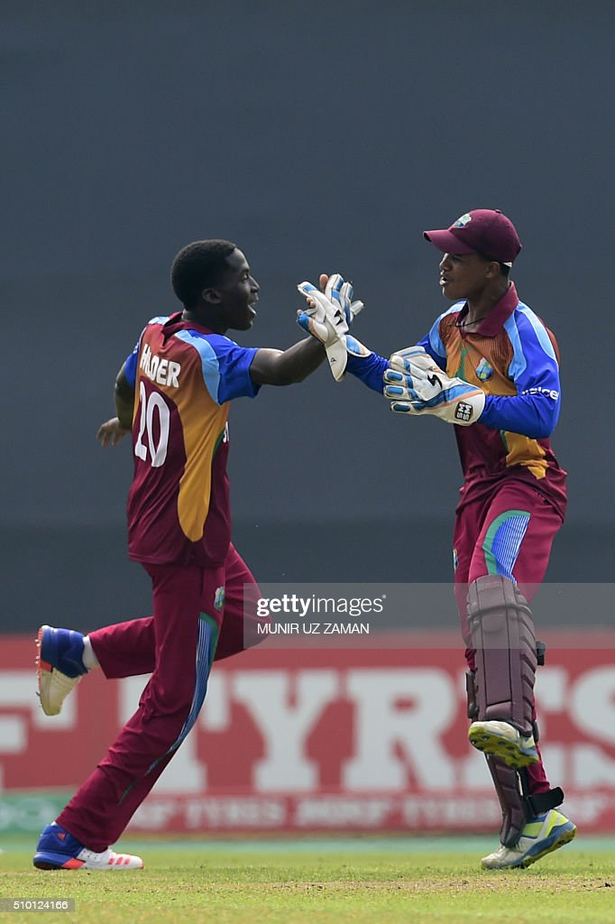 West Indies cricketer Chemar K Holder (L) celebrates with his teammate Tevin Imlach (R) after the dismissal of the Indian cricketer Mahipal Lomror during the under-19s World Cup cricket final between India and West Indies at the Sher-e-Bangla National Cricket Stadium in Dhaka on February 14, 2016. AFP PHOTO/Munir uz ZAMAN / AFP / MUNIR UZ ZAMAN