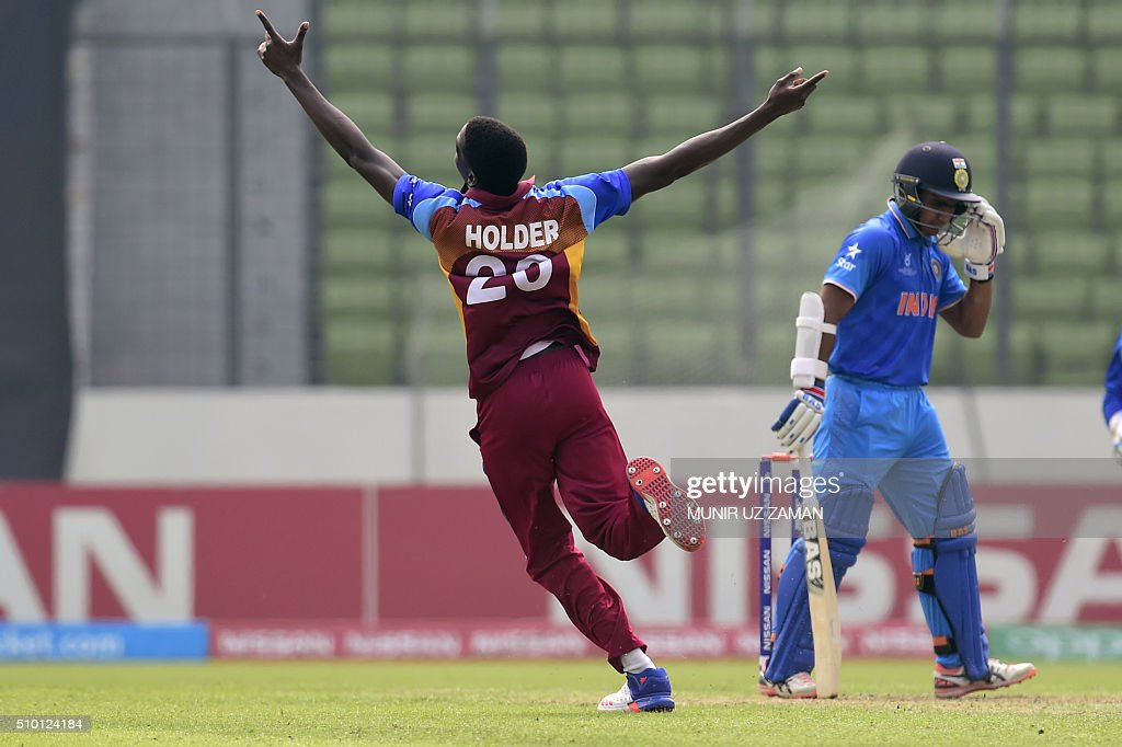 West Indies cricketer Chemar K Holder (L) reacts after the dismissal of the Indian cricketer Mahipal Lomror (R) during the under-19s World Cup cricket final between India and West Indies at the Sher-e-Bangla National Cricket Stadium in Dhaka on February 14, 2016. AFP PHOTO/Munir uz ZAMAN / AFP / MUNIR UZ ZAMAN
