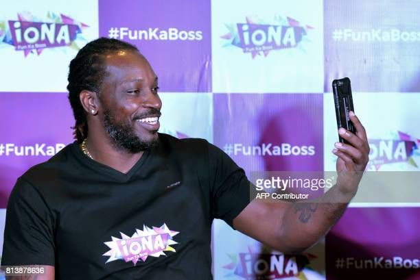 West Indies cricketer Chris Gayle takes a picture during a press conference to announce the partnering of the cricketer with Iona Entertainment and...