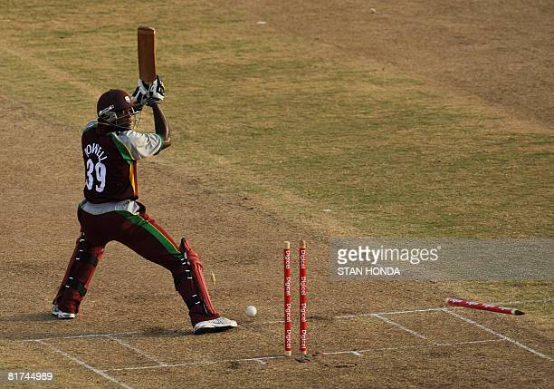 West Indies cricketer Daren Powell looks back to see his wickets uprooted by Australia cricketer Shane Watson June 27 2008 at National Stadium in St...