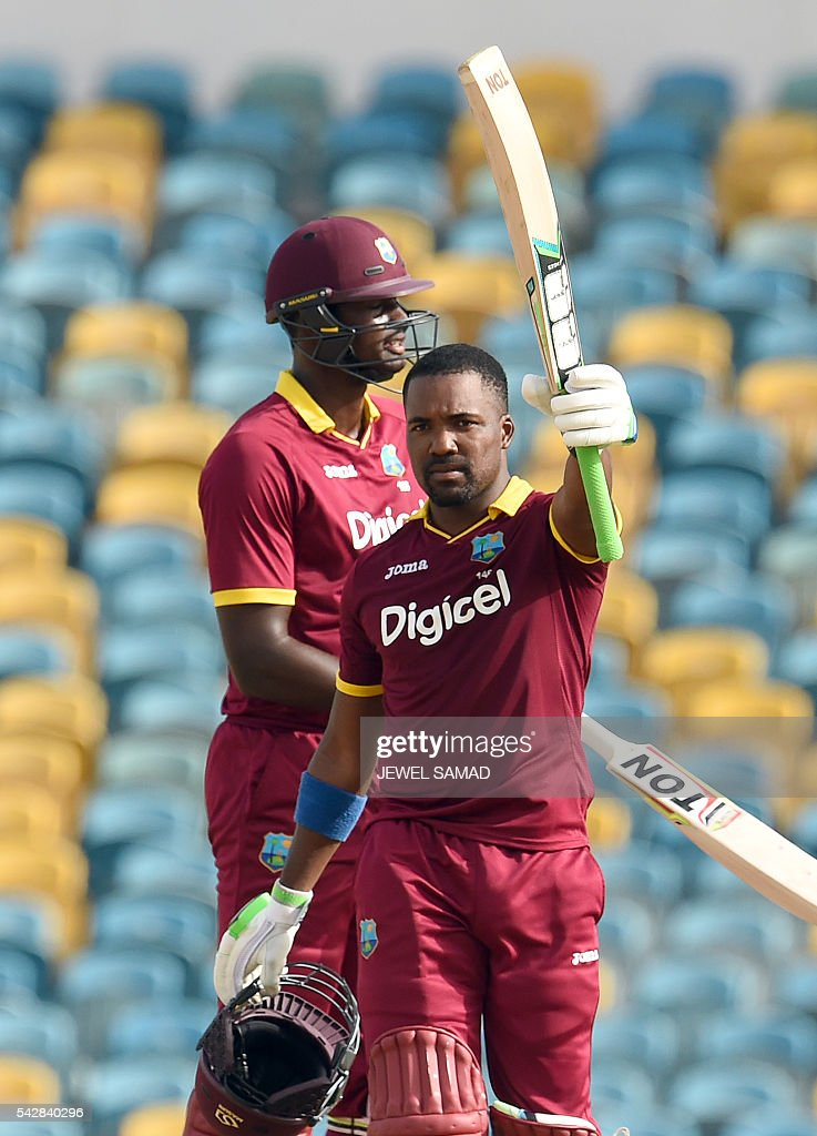 West Indies cricketer Darren Bravo celebrates after scoring his century as team captain Jason Holder looks on during the 9th One Day International match of the Tri-nation Series between South Africa and West Indies at the Kensington Oval stadium in Bridgetown on June 24, 2016. / AFP / JEWEL