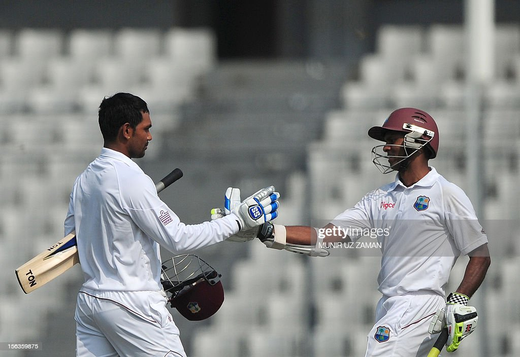 West Indies cricketer Denesh Ramdin (L) shakes hands with teammate Shivnarine Chanderpaul after scoring a century during the second day of the first Test match between Bangladesh and West Indies at the Sher-e-Bangla National Cricket Stadium in Dhaka on November 14, 2012. AFP PHOTO/ Munir uz ZAMAN