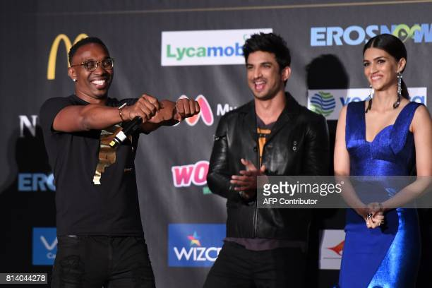 West Indies cricketer Dwayne Bravo is joined by Bollywood actor Sushant Singh Rajput and actress Kriti Sanon as he signs during a press conference...