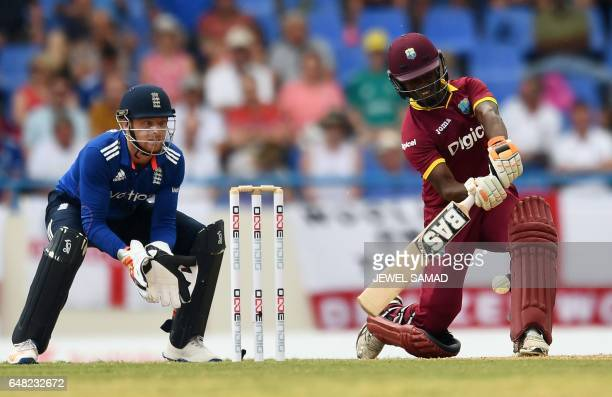 West Indies cricketer Jason Mohammed plays a shot as Englands cricket team wicketkeeper Jos Buttler looks on during the second of the threematch One...