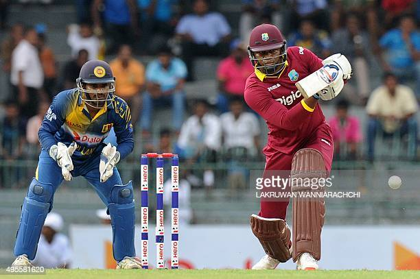West Indies cricketer Marlon Samuels plays a shot as Sri Lanakan wicketkeeper Kusal Janith Perera looks on during the second One Day International...