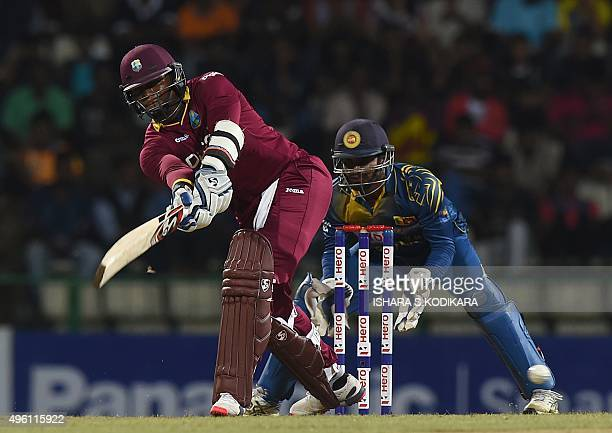 West Indies cricketer Marlon Samuels plays a shot as Sri Lankan wicketkeeper Kusal Janith Perera looks on during the third and final One Day...