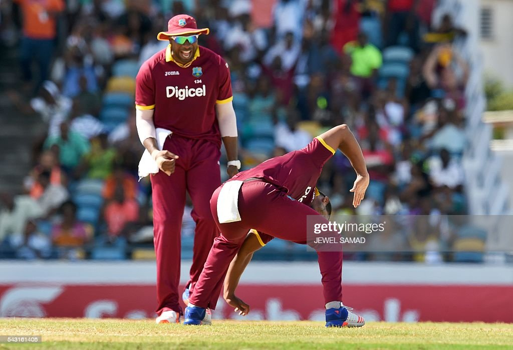 West Indies cricketer Shannon Gabriel (R) and his teammate Kieron Pollard celebrate the dismissal of Australian batsman Glenn Maxwell during the final match of the Tri-nation Series between Australia and West Indies in Bridgetown on June 26, 2016. / AFP / Jewel SAMAD