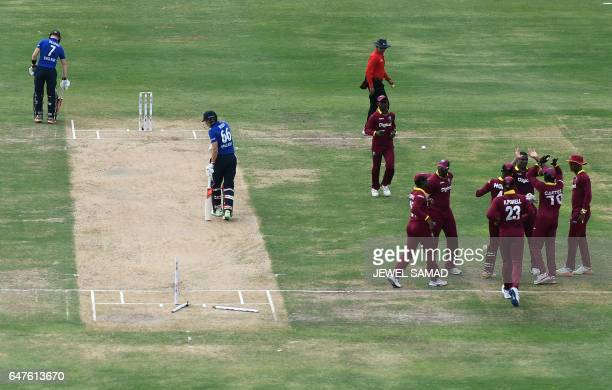 West Indies cricketer Shannon Gabriel celebrates with teammates affter bowling out England's Joe Root during the One Day International match between...