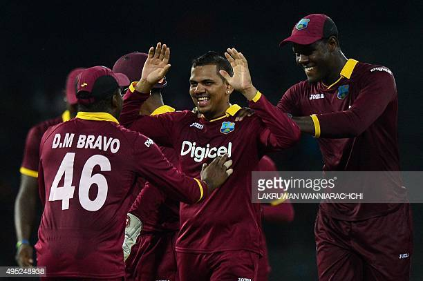 West Indies Cricketer Sunil Narine celebrates with his teammates after he dismissed Sri Lanka's Cricketer Shehan Jayasuriya during the first One Day...