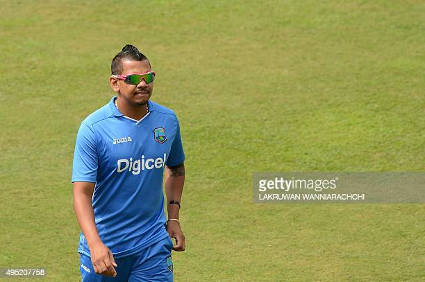 West Indies cricketer Sunil Narine walks after rain showers delayed the start of play on the first One Day International match between Sri Lanka and...