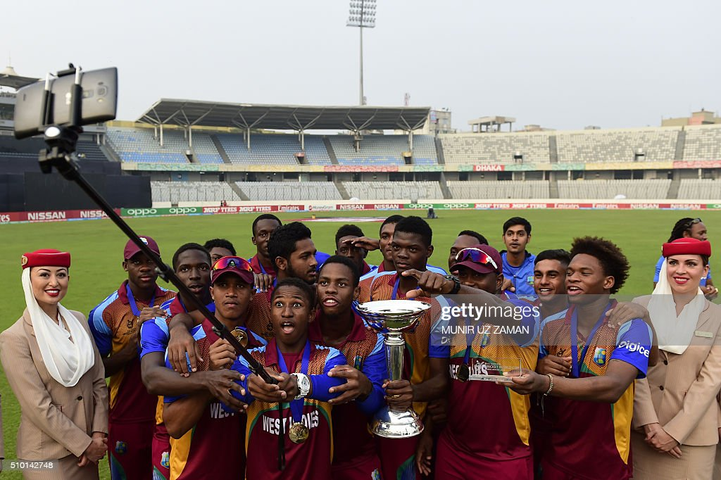 West Indies cricketers take a 'selfie' as they pose with the trophy after winning the Under-19 World Cup cricket final between India and West Indies at the The Sher-e-Bangla National Cricket Stadium in Dhaka on February 14, 2016. AFP PHOTO / Munir uz ZAMAN / AFP / MUNIR UZ ZAMAN