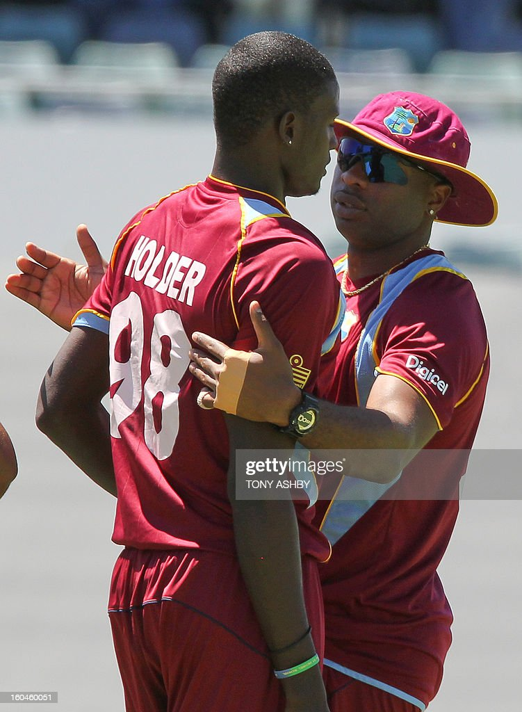 West Indies fast bowler Jason Holder (L) is congratulated by his teamate Kieron Pollard (R) after taking the wicket of Australia's batsman Aaron Finch during the one-day international cricket match between Australia and the West Indies at the WACA ground on February 1, 2013. AFP PHOTO/Tony ASHBY IMAGE