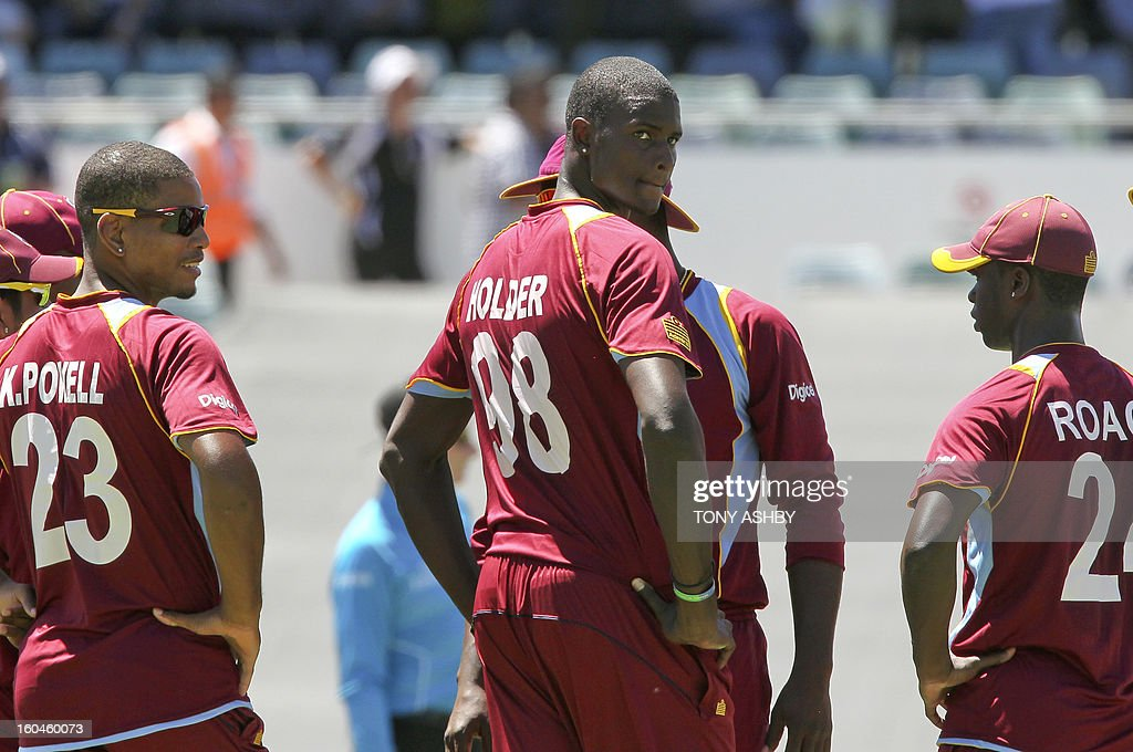 West Indies fast bowler Jason Holder (C) waits on the referral with teamates Kieran Powell (L) and Kemar Roach (R) after taking the wicket of Australia's batsman Aaron Finch (not pictured) during the one-day international cricket match between Australia and the West Indies at the WACA ground on February 1, 2013. AFP PHOTO/Tony ASHBY IMAGE
