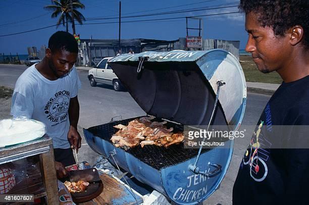West Indies Jamaica Market Man cooking jerk chicken on roadside stall with waiting customer