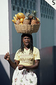 West Indies, Jamaica, woman carrying basket of fruit on head