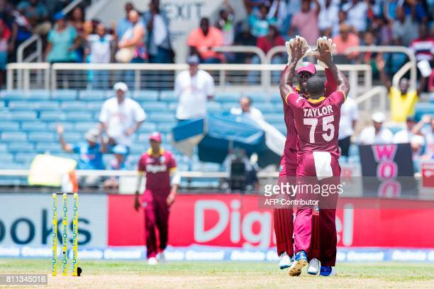 West Indies' Jerome Taylor and wicketkeeper Chadwick Walton celebrate after catching out India's Kedar Jadhav during the T20 match between West...