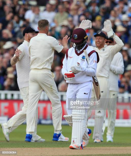 West Indies' Kemar Roach walks back to the pavilion as England players celebrate taking his wicket behind during play on day 3 of the first Test...