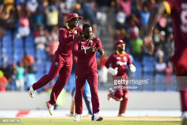 West Indies' Kesrick Williams celebrates with teammates after dismissing India's MS Dhoni during the fourth One Day International match between West...