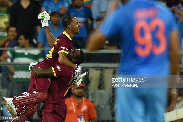 West Indies Lendl Simmons celebrates with a teammate after winning the World T20 cricket tournament semifinal match against India at The Wankhede...