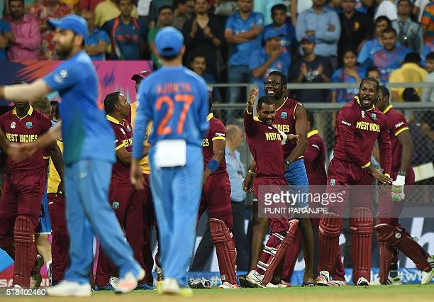 West Indies players including Chris Gayle celebrate after winning the World T20 cricket tournament semifinal match against India at The Wankhede...